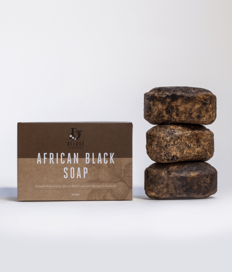 Three bars of Deluxe African Black Soap bar next to product box.